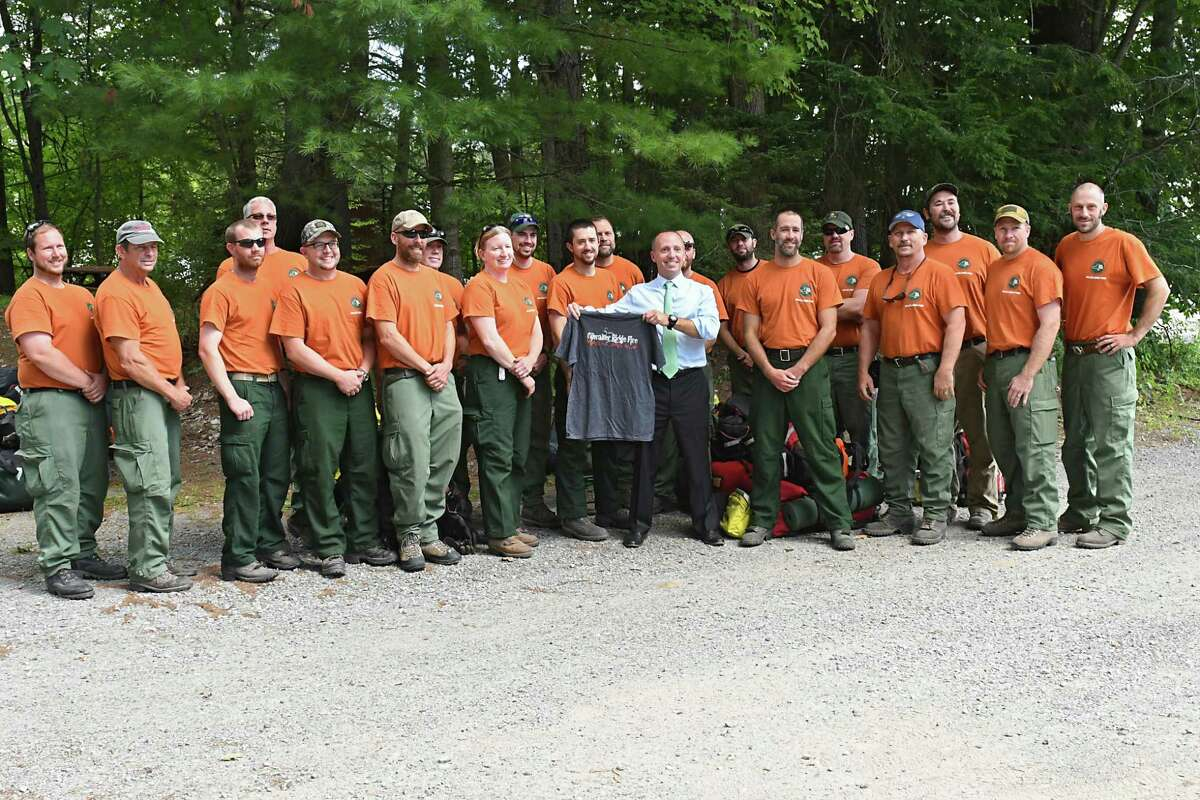 The New York State Department of Environmental Conservation Commissioner Basil Seggos holds up a t-shirt given to him by wildfire fighters returning from fighting Montana wildfire at the Saratoga Tree Nursery on Thursday, Aug. 24, 2017 in Saratoga Springs, N.Y. The crew, which includes Forest Rangers, DEC employees from various fields, and volunteers, is made up of residents from across the state. (Lori Van Buren / Times Union)