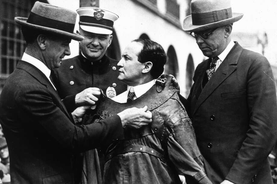 Hungarian born magician and escapologist Harry Houdini (1874 - 1926) being fitted into an escape proof suit.   (Photo by MPI/Getty Images) Photo: MPI/Getty Images