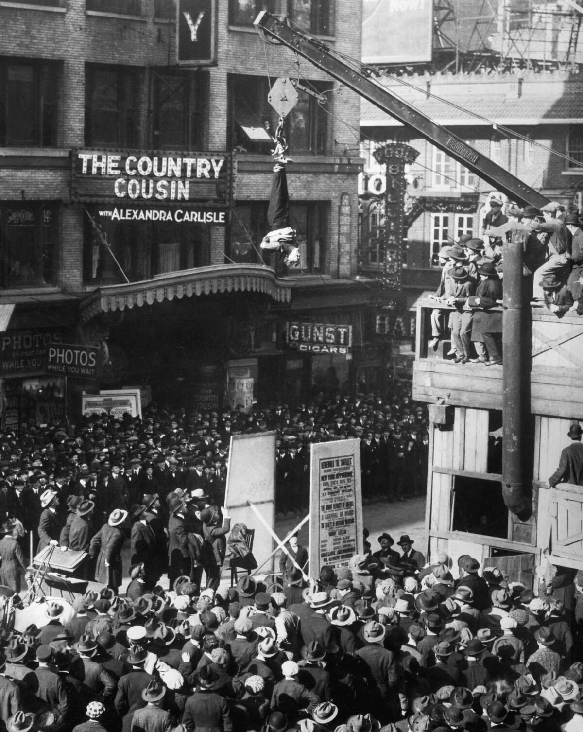 Harry Houdini slipping out of a straitjacket while hanging upside down over Broadway and 46th street in New York City.