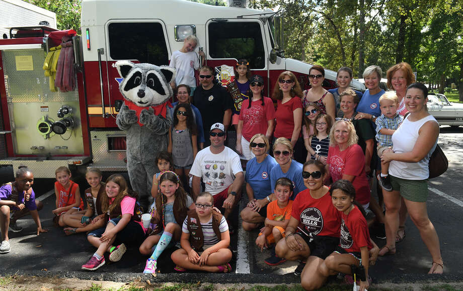 "Justis Benavides, 16, back left, a Kingwood Park High School sophomore, dressed as ""Woody the Raccoon"", the Woodland Hills Elementary School mascot, teams up for a photo with his friends and members of the East Montgomery County Fire Department during the South Woodland Hills Community ""Back 2 School"" at their community room and park on August 19, 2017. (Photo by Jerry Baker/Freelance) Photo: Jerry Baker, Freelance / Freelance"