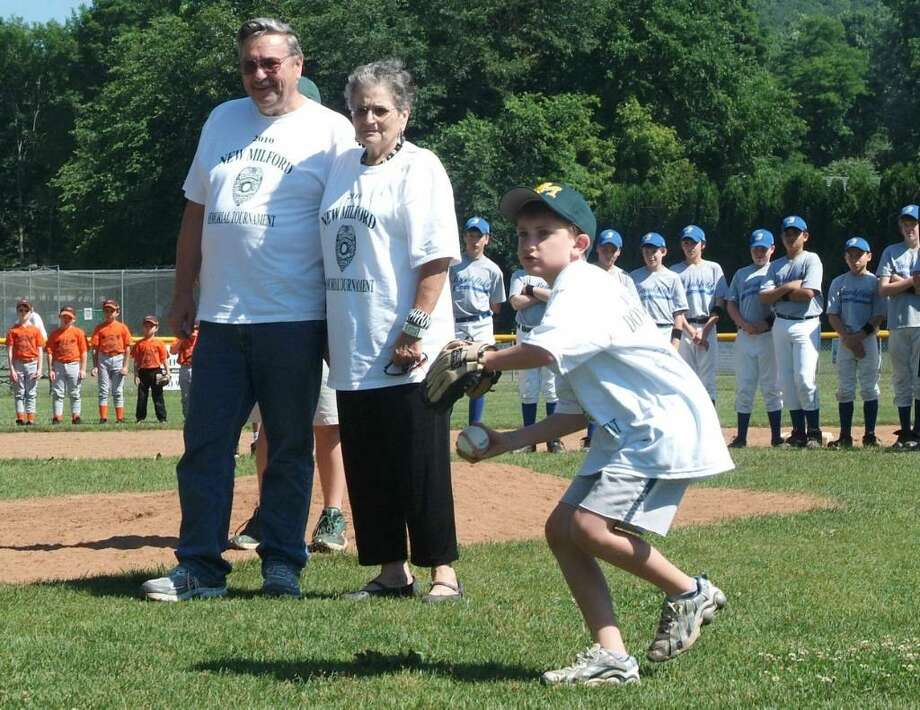 Eight year old, Matthew Hassiak, of New Milford, throws the ceremonial first pitch at the opening of the New Milford Youth Baseball / Softball Tournament, in honor of his father, Danbury police officer, Donald Hassiak,  who was killed in a hit and run accident earlier in the month. Hassiak is joined on the mound with his grandparents, Mr. & Mrs. Donald Hassiak Sr .Photo taken: Saturday, June 19, 2010. Photo: Jay Weir / The News-Times Freelance