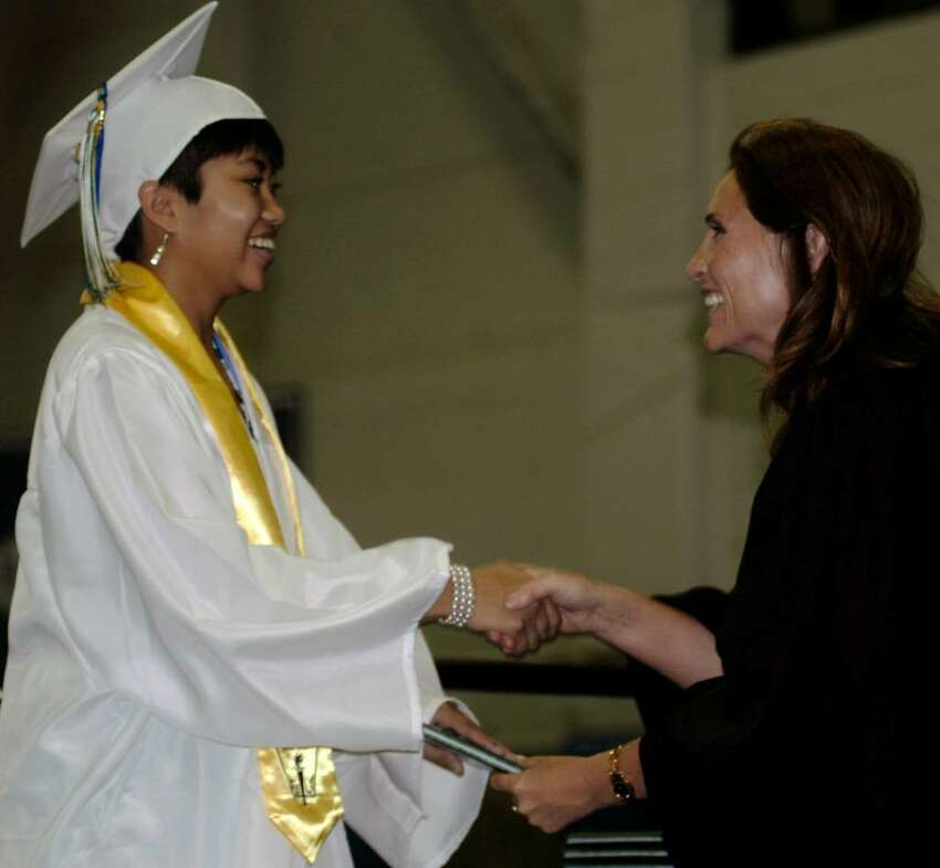 Elizabeth Marandola is a happy graduate as she accepts her diploma Saturday from Board of Education chairman Wendy Faulenbach during New Milford High School's commencement exercises at the O'Neill Center in Danbury.