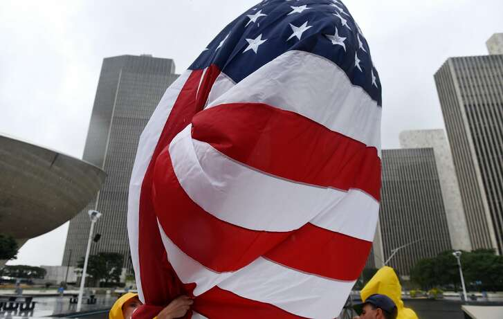 A replacement American flag is raised in the Empire State Plaza by workers from the State Office of General Services on Friday, Aug. 18, 2017, in Albany, N.Y. The flags replaced when they become worn. The previous flag had a broken grommet. (Will Waldron/Times Union)