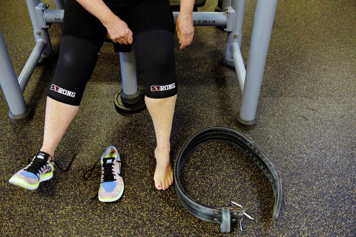 Marilyn Cataldo puts on knee braces before performing squats at Best Fitness on Thursday, Aug. 24, 2017, in Albany, N.Y. (Paul Buckowski / Times Union)