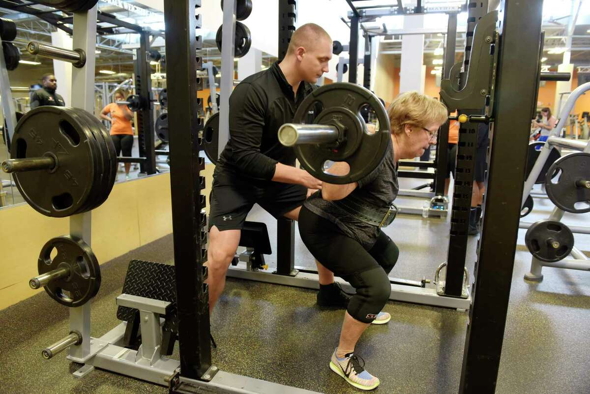 Marilyn Cataldo performs a squat as she works out with her personal trainer, David Derry, Jr., at Best Fitness on Thursday, Aug. 24, 2017, in Albany, N.Y. (Paul Buckowski / Times Union)