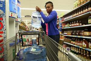 Marie Michel loads a filled water bottled into her shopping cart inside the Kroger on Buffalo Speedway in preparation for tropical storm Harvey Thursday, Aug. 24, 2017, in Houston. The storm is estimated to make landfall Friday. ( Godofredo A. Vasquez / Houston Chronicle )