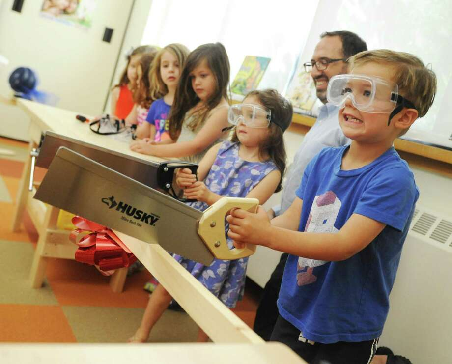 "Oliver Halio, of Riverside, takes part in the ""ribbon-sawing"" at the grand opening of the new STEAM room at Temple Sholom's Selma Maisel Nursery School in Greenwich, Conn. Thursday, Aug. 24, 2017. The new room features work benches, water tables, programmable robotic toys, wooden ramps and a giant wind tunnel. Photo: Tyler Sizemore / Hearst Connecticut Media / Greenwich Time"