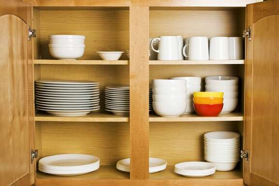 Open wood cupboard shelving plates dishes and jugs Dishes neatly stacked in wood cabinets. Details Credit: klosfoto