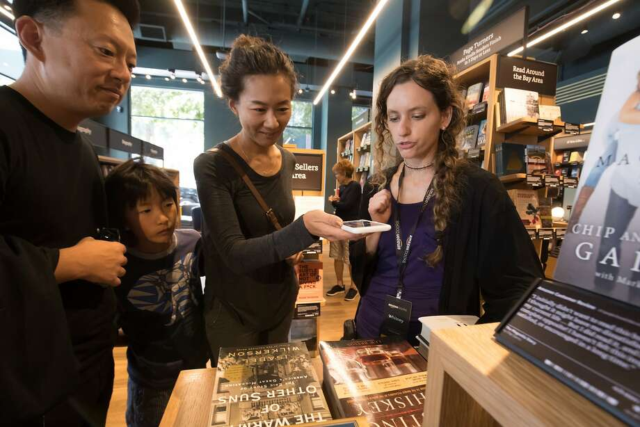 Whitney Chessum (right) assists Patrick Chung (left), Cooper Chung, 9, and Gina Kim at the store. Photo: Paul Kuroda, Special To The Chronicle
