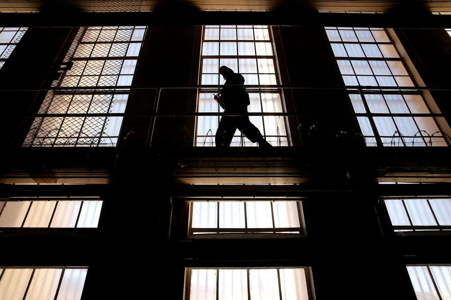A guard on the catwalk above the cells of the condemned in East Block on death row at San Quentin State Prison on Tuesday December 29, 2015, in San Quentin, Calif. Photo: Michael Macor / The Chronicle