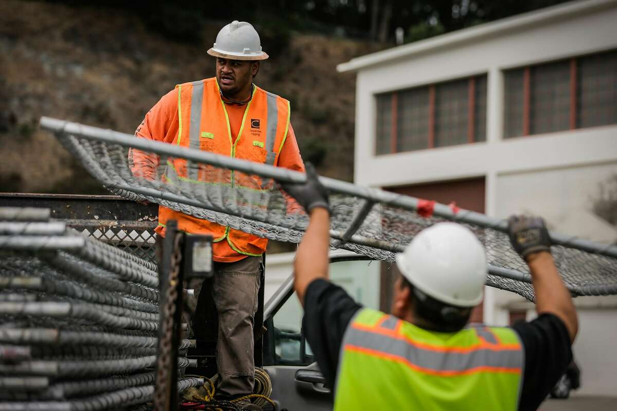 Workers Mario T. (left) and Raul Marquez (right) unload chain link fences from a truck ahead of Saturday's Patriot Prayer rally at Crissy Field in San Francisco, Calif., on Thursday, Aug. 24, 2017.