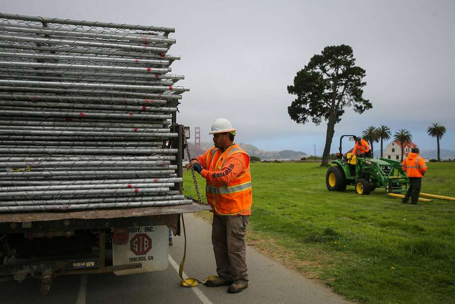 A worker prepares to unload a truckload of chain-link fencing at Crissy Field before Saturday's Patriot Prayer rally. Photo: Gabrielle Lurie, The Chronicle
