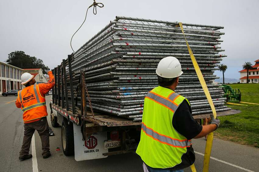 Workers Mario T. (left) and Raul Marquez (right) prepare to unload a truck full of chain link fences at Crissy Field ahead of Saturday's Patriot Prayer rally in San Francisco, Calif., on Thursday, Aug. 24, 2017.