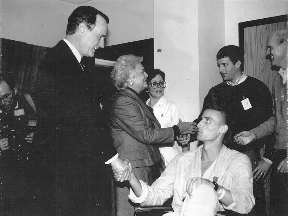 Army Sgt. Kyle Kelley looks up at President George H.W. Bush during Bush's visit to soldiers wounded in Panama recovering at Wilford Hall Medical Center on Dec. 31, 1989. Kelley, 20, received fragment wounds in his lower back on Dec. 20. He is from Santee, Calif., and has served in the Army nearly three years. San Antonio Light file photo