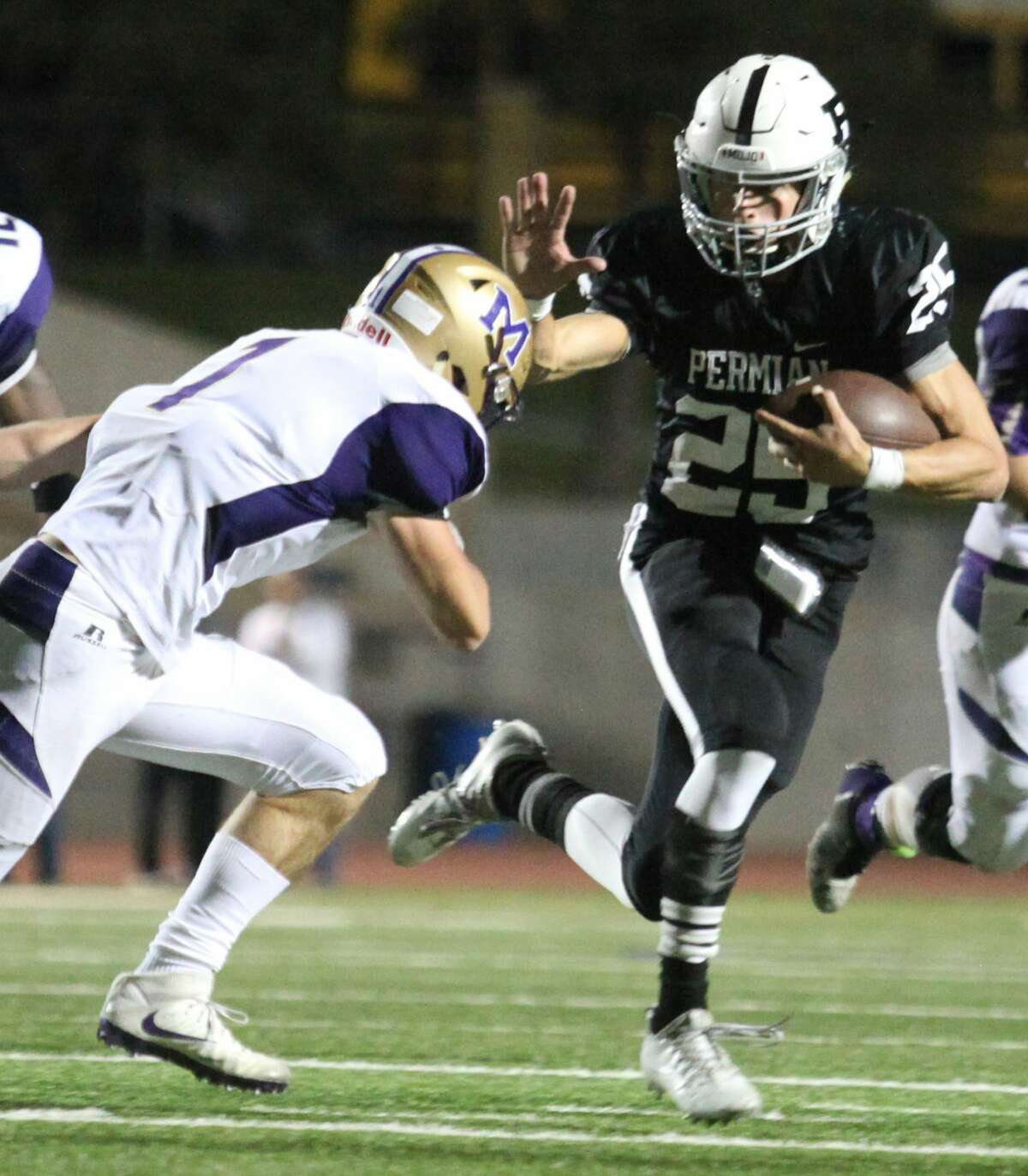 Permian Panthers' quarterback Steve Steen, 25, attempts to stiff arms Midland Bulldogs' McLane Mannix, 1, during the first quarter Friday night at Ratliff Stadium.