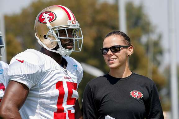 San Francisco 49ers assistant coach Katie Sowers talks with wide receiver Pierre Garcon during practice at the San Francisco 49ers training facility on Wednesday, August 23, 2017, in Santa Clara, California. Sowers, 31, made more history, becoming the NFL's first openly gay coach. San Francisco 49ers officially hired Katie Sowers for the 2017 season last week, making her the team's first female assistant coach.