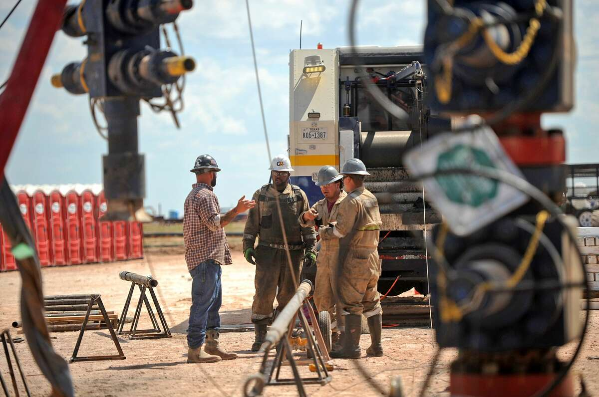 """Octane Energy well-site leader Justin """"Bull"""" Smith (left) talks with a GR Energy Services wireline crew at a fracking site managed by Octane Energy on Friday, Sept. 23, 2016 near Stanton. James Durbin/Reporter-Telegram"""