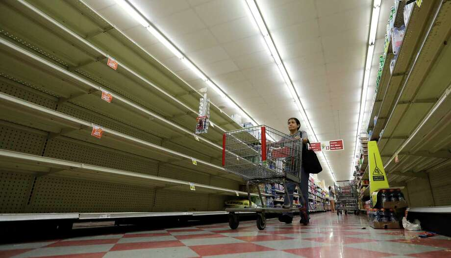 Shoppers pass empty shelves along the bottled water isle in a Houston grocery store as Hurricane Harvey intensifies in the Gulf of Mexico, Thursday, Aug. 24, 2017.  CONTINUE to see which cities had the most investigative demands for price gouging from the Texas Attorney General. Photo: David J. Phillip, Associated Press / Copyright 2017 The Associated Press. All rights reserved.