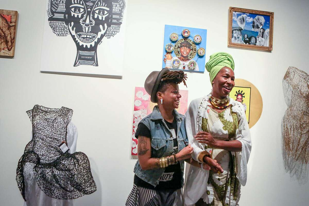 Karen Seneferu (right), founder and co-curator, and Melorra Green, curator, share a moment at the Black Woman Is God exhibition at SOMArts on Wednesday, August 23, 2017 in San Francisco, Calif.