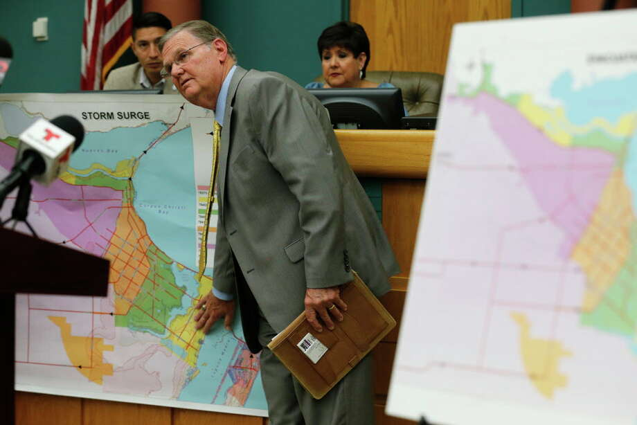Corpus Christi mayor Joe McComb (center) points to a map of low lying areas in the city whose residents have been asked to voluntarily evacuate due to the impending landfall of Hurricane Harvey on Thursday, Aug. 24, 2017. Concerns over the growing tropical storm has moved officials to ask citizens to voluntarily leave Corpus Christi. Port Aransas was under a mandatory evacuation though some residents have opted to ride out the storm. Photo: Kin Man Hui, San Antonio Express-News / ©2017 San Antonio Express-News