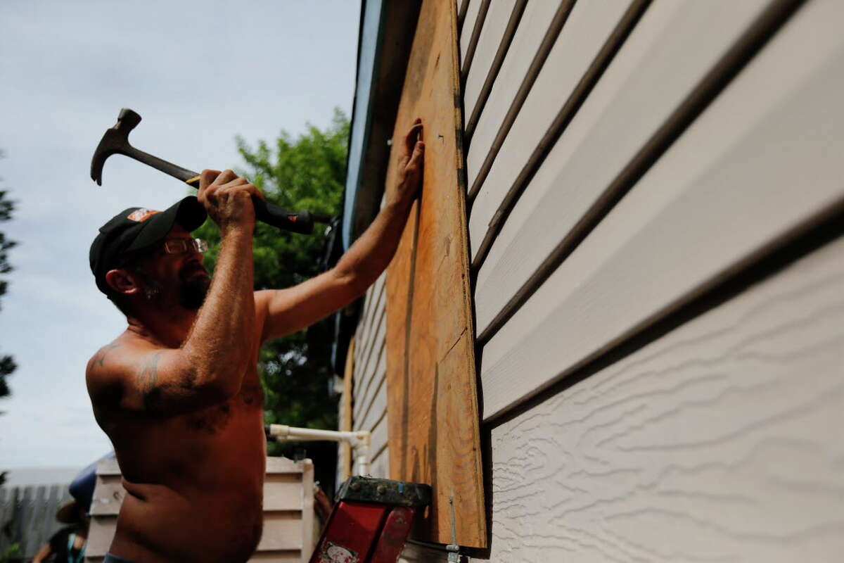 Port Aransas resident Erick Shamp pounds a nail into a piece of plywood to cover a window on Thursday, Aug. 24, 2017.