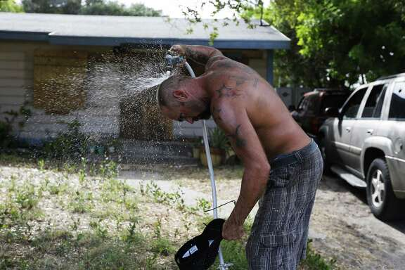Port Aransas resident Erick Shamp sprays water on himself to cool off after boarding up windows for his mother's home and a friend's home on Thursday, Aug. 24, 2017. The residents of Corpus Christi, Port Aransas and other surrounding gulf coast towns brace for the impending landfall of Hurricane Harvey. Concerns over the growing tropical storm has moved officials to ask citizens to voluntarily leave Corpus Christi. Port Aransas were under a mandatory evacuation though some residents like Shamp have opted to ride out the storm. (Kin Man Hui/San Antonio Express-News)