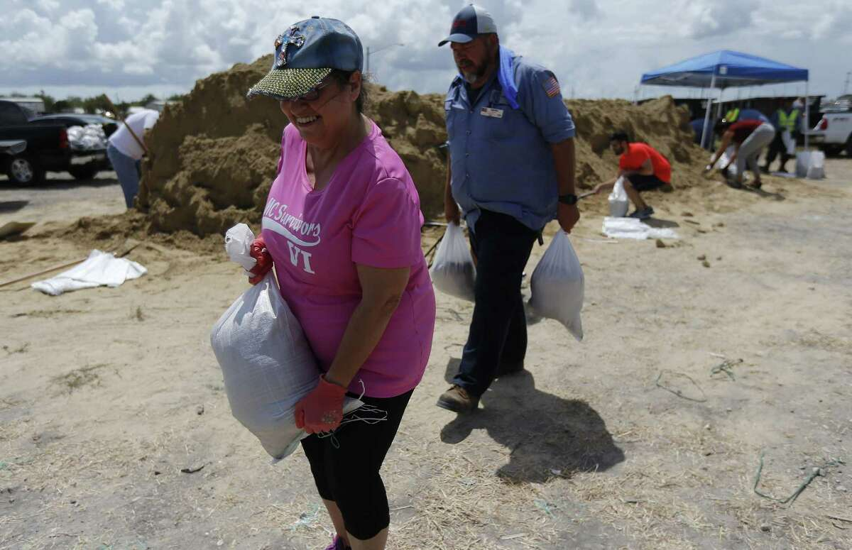 Corpus Christi resident Thelma Munoz (front) carries a bag of sand to her car as she prepares for Hurricane Harvey on Thursday, Aug. 24, 2017. Corpus Christi, Port Aransas and other surrounding gulf coast towns braced for the impending landfall of Hurricane Harvey. Concerns over the growing tropical storm have moved officials to ask citizens to voluntarily leave Corpus Christi. Port Aransas was under a mandatory evacuation though some residents have opted to ride out the storm. (Kin Man Hui/San Antonio Express-News)