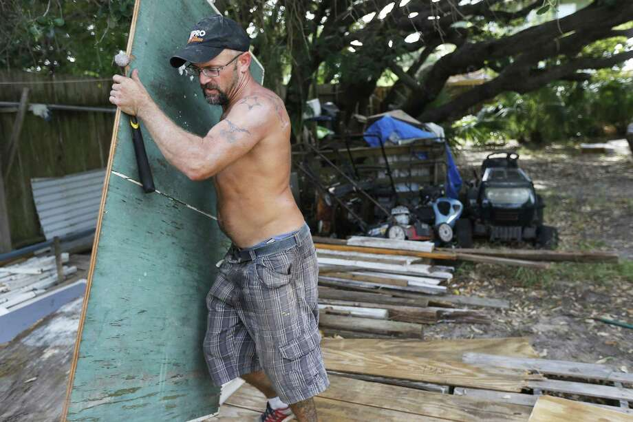 Port Aransas resident Erick Shamp grabs a section of spare wood from a dismantled ping pong table to use for boarding up a window on Thursday, Aug. 24, 2017. The residents of Corpus Christi, Port Aransas and other surrounding gulf coast towns brace for the impending landfall of Hurricane Harvey. Concerns over the growing tropical storm has moved officials to ask citizens to voluntarily leave Corpus Christi. Port Aransas were under a mandatory evacuation though some residents like Shamp have opted to ride out the storm. (Kin Man Hui/San Antonio Express-News) Photo: Kin Man Hui, Staff / San Antonio Express-News / ©2017 San Antonio Express-News