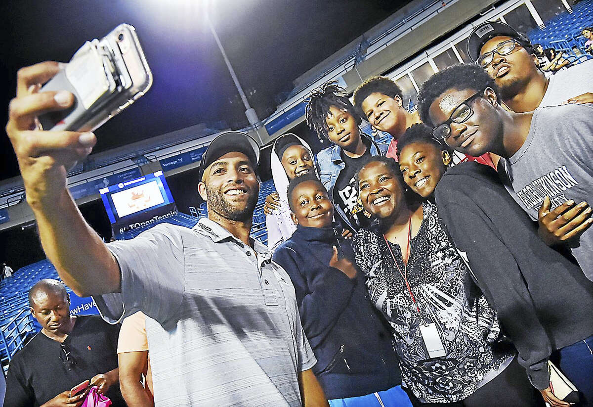 James Blake takes a selfie with people from Hall Neighborhood House in Bridgeport after defeating Michael Chang 7-5 in the Men's Legends Event at the Connecticut Open on Thursday.