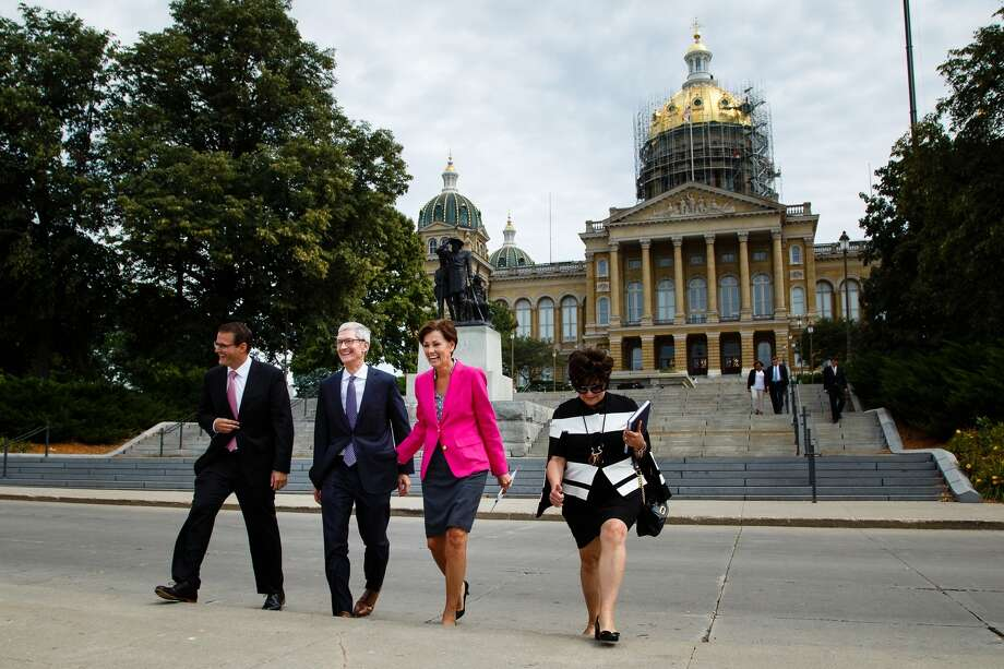 Apple CEO Tim Cook, second from left, and Iowa Gov. Kim Reynolds, third from left, walk to a podium in front of the Capitol building, background, in Des Moines, Iowa, Thursday, Aug. 24, 2017, to announce Apple's plans for two new data storage centers and to create at least 50 jobs near Des Moines. (Brian Powers/The Des Moines Register via AP) Photo: Brian Powers, MBR / The Des Moines Register