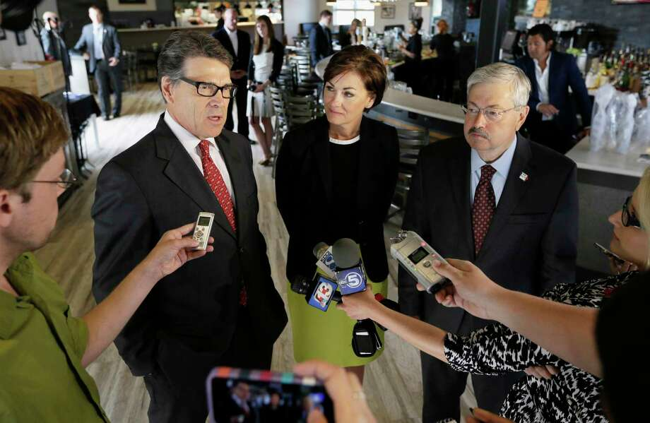 FILE-- In this May 29, 2014, file photo, Texas Gov. Rick Perry, left, accompanied by Iowa Lt. Gov. Kim Reynolds, center, and Iowa Gov. Terry Branstad speaks to reporters following a fund-raising breakfast for Branstad in Ames, Iowa. Branstad has been working hard to spread the word that the Iowa Republican Party and the state's lead-off presidential caucuses are welcoming to all Republicans. (AP Photo/Charlie Neibergall) Photo: Charlie Neibergall, STF / AP