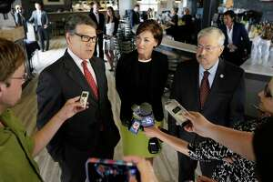 FILE-- In this May 29, 2014, file photo, Texas Gov. Rick Perry, left, accompanied by Iowa Lt. Gov. Kim Reynolds, center, and Iowa Gov. Terry Branstad speaks to reporters following a fund-raising breakfast for Branstad in Ames, Iowa. Branstad has been working hard to spread the word that the Iowa Republican Party and the state's lead-off presidential caucuses are welcoming to all Republicans. (AP Photo/Charlie Neibergall)