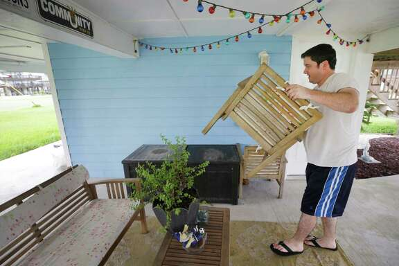 Tim Foley secures patio furniture below in his home in the community of Sea Isle as he prepares for Hurricane Harvey Thursday, Aug. 24, 2017, in Galveston. He plans to stay at his home during the hurricane.