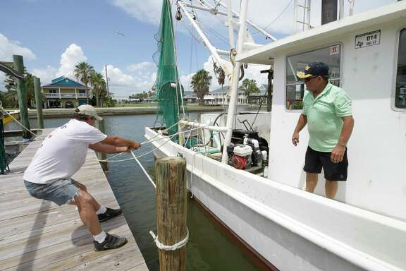 Steve Elliott, left, and David Prater, right, secure a 40 foot shrimp boat at West End Marina Thursday, Aug. 24, 2017, in Galveston as people prepare for Hurricane Harvey.