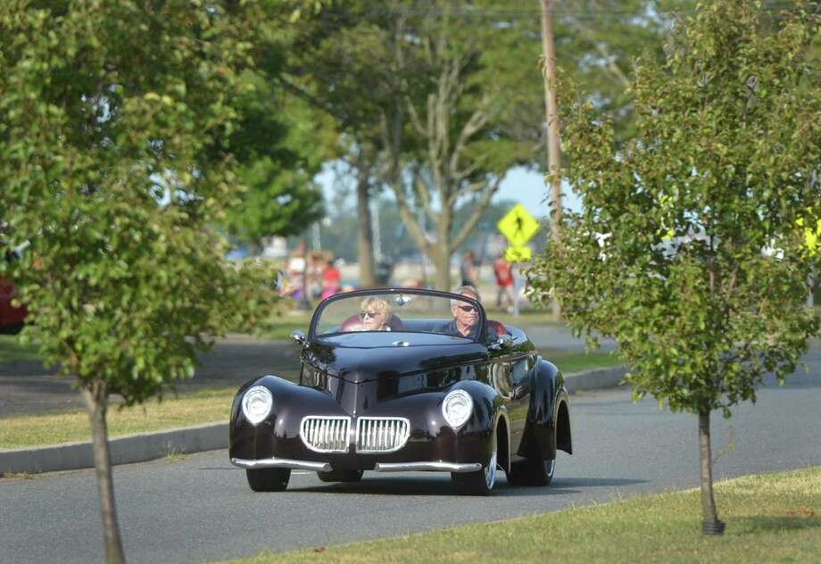 Lilli and Charlie Stuart from Darien make their way into the Coachmen Rod and Custom Car Club Summer Beach Cruise in their unique 1940 Willys Swoopster on Aug. 17 at Calf Pasture Beach in Norwalk. Photo: Alex Von Kleydorff / Hearst Connecticut Media / Norwalk Hour
