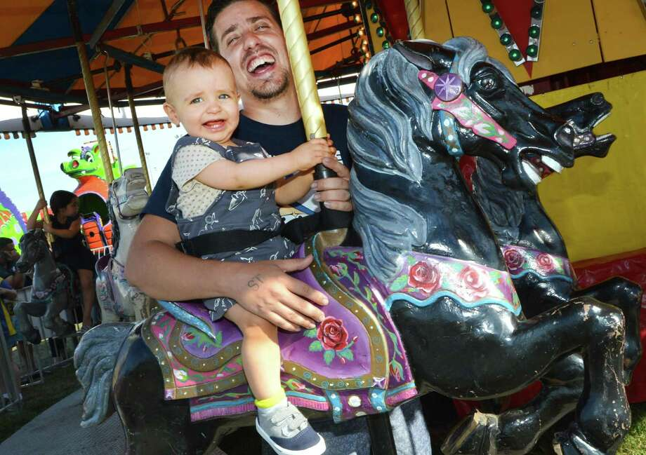 Francisco Sendra holds onto his son 15-month-old son Benjamin as they both laugh while riding the carousel on the final day of the Norwalk Seaport Association's Oyster Festival on Sunday, Sept. 11, 2016 in Veteran's Memorial Park in Norwalk. Photo: Alex Von Kleydorff / Hearst Connecticut Media / Connecticut Post