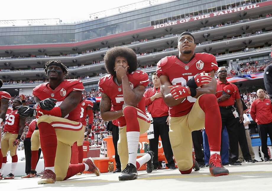 FILE - In this Oct. 2, 2016, file photo, from left, San Francisco 49ers outside linebacker Eli Harold, quarterback Colin Kaepernick, center, and safety Eric Reid kneel during the national anthem before an NFL football game against the Dallas Cowboys in Santa Clara, Calif. What started as a protest against police brutality has mushroomed a year later into a divisive debate over the future of Kaepernick who refused to stand for the national anthem and now faces what his fans see as blackballing for speaking out in a country roiled by racial strife. The once-rising star and Super Bowl quarterback has been unemployed since March, when he opted out of his contract and became a free agent who could sign with any team. (AP Photo/Marcio Jose Sanchez, File) Photo: Marcio Jose Sanchez, Associated Press