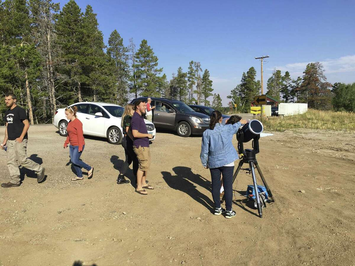 Nina Chevalier, in denim jacket, a member of the San Antonio League of Sidewalk Astronomers, adjusts a telescope at her eclipse viewing spot in Wyoming.