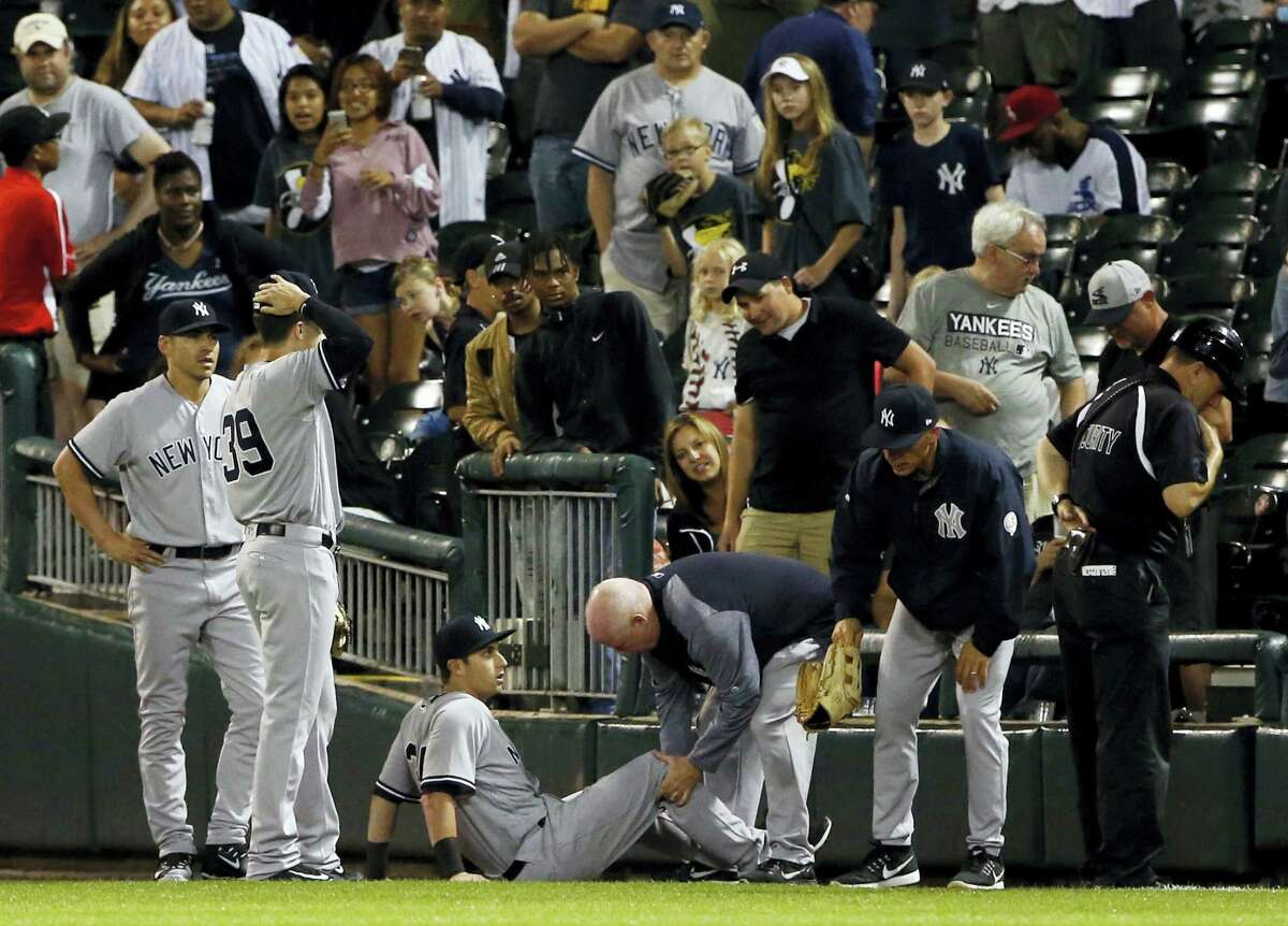 The Yankees' Dustin Fowler is checked by a team trainer after getting injured in the first inning Thursday in Chicago.