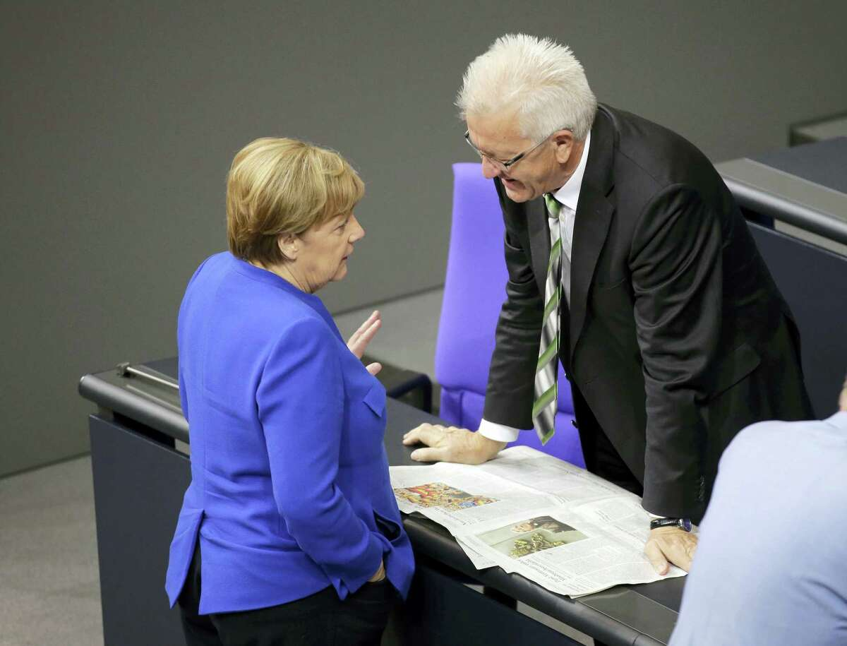 German Chancellor Angela Merkel, left, talks to Baden-Wuerttemberg governor Winfried Kretschmann of the Green Party prior to a debate of the German parliament Bundestag on the gay marriage in Berlin, Germany, Friday, June 30, 2017.