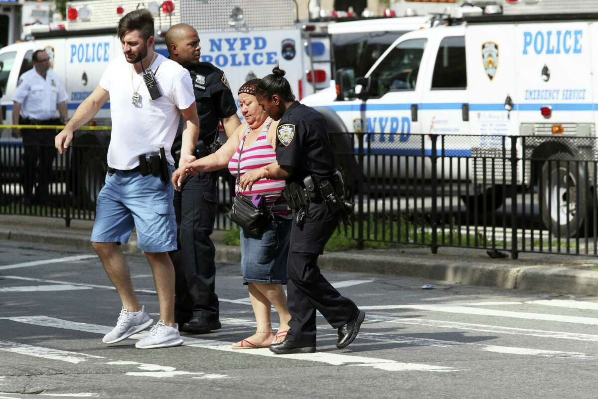 Police help people cross the street outside the Bronx Lebanon Hospital in New York after a gunman opened fire there on Friday, June 30, 2017. The gunman, identified as Dr. Henry Bello who used to work at the hospital, returned with a rifle hidden under his white lab coat, law enforcement officials said.