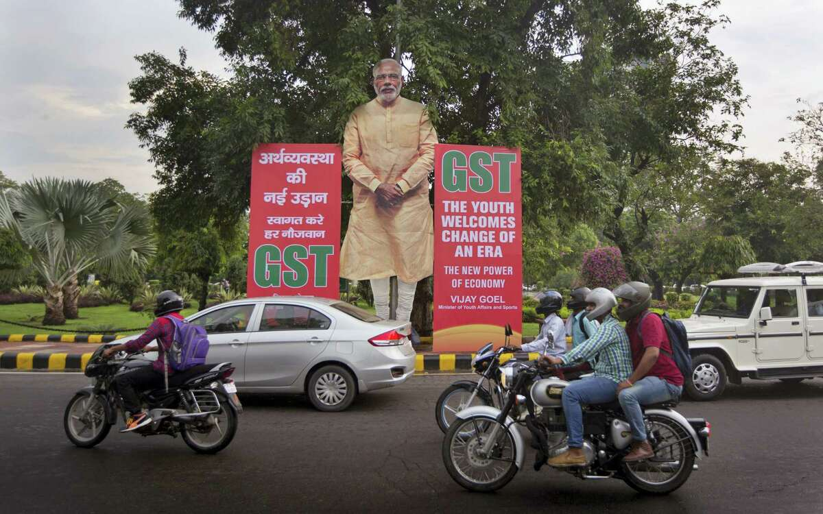 Indian commuters drive past a huge cutout of Indian Prime Minister Narendra Modi next to Goods and Services Tax (GST) banners in New Delhi, India, Friday, June 30, 2017. From July 1 Indian government is introducing a new tax regime called GST, a single, nationwide tax replacing a complicated mix of state and federal taxes and will change the cost of nearly everything people buy.