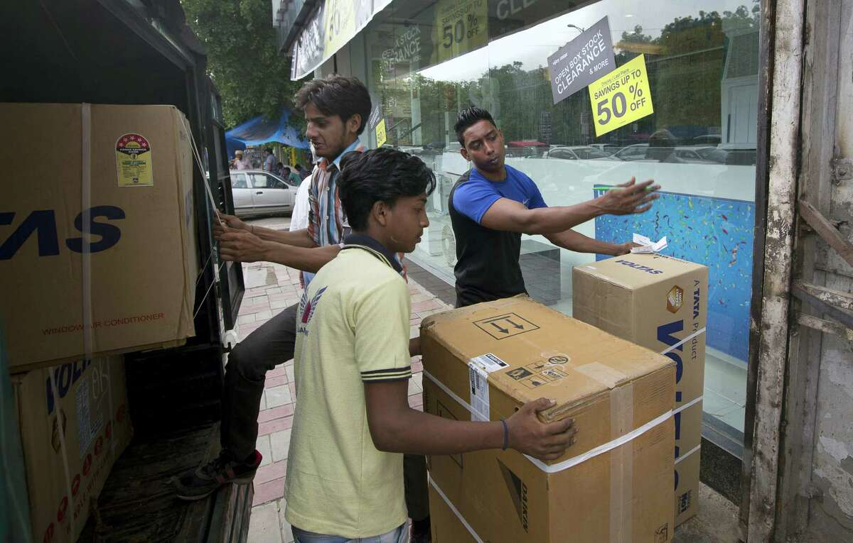 In this Thursday, June 29, 2017 photo, Indian laborers unload electronic goods to deliver to a shop ahead of the implementation of the Goods and Services Tax (GST) at Lajpat Nagar market in New Delhi, India, Thursday, June 29, 2017. As India readies itself for a massive tax overhaul the crowded New Delhi market of Lajpat Nagar is plastered with posters announcing massive sales and shoppers are vacuuming up household gadgets and high-end electronics that will cost more from July 1. Retailers want to clear their inventories before the new tax model kicks in for fear they may end up incurring fresh taxes on items they bought earlier from manufacturers. (AP Photo/Manish Swarup)