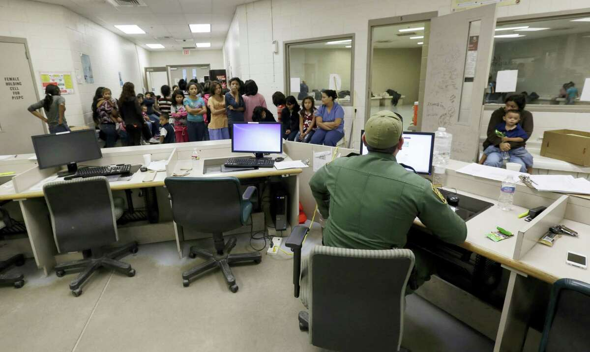 "This June 18, 2014, file photo shows U.S. Customs and Border Protection agents work at a processing facility in Brownsville,Texas. A new ""surge initiative"" aims to identify and arrest the adult sponsors of unaccompanied minors who paid coyotes or other smuggling operations to bring young people across the U.S. border, Immigration and Customs Enforcement officials confirmed Thursday, June 29, 2017."