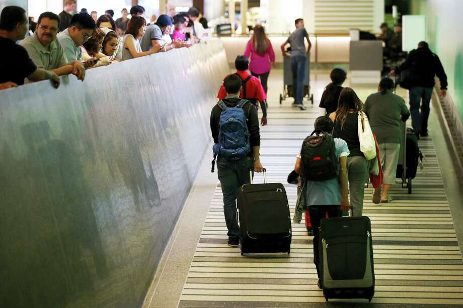 Travelers make their way up the arrival ramp at the Tom Bradley International Terminal at the Los Angeles International Airport Thursday, June 29, 2017, in Los Angeles. After months of wrangling, tighter restrictions on travel to the U.S. from six mostly Muslim nations take effect Thursday evening after the Supreme Court gave its go-ahead for a limited version of President Donald Trump's plans for a ban. Photo: Jae C. Hong / AP Photo  / Copyright 2017 The Associated Press. All rights reserved.
