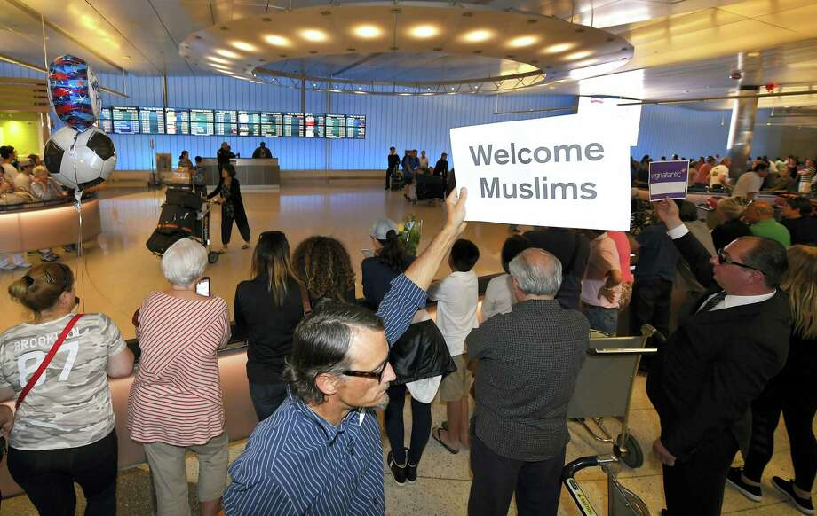John Wider holds up a sign becoming Muslims in the Tom Bradley International Terminal at Los Angeles International Airport, Thursday, June 29, 2017, in Los Angeles. A scaled-back version of President Donald Trump's travel ban took effect Thursday evening, stripped of provisions that brought protests and chaos at airports worldwide in January yet still likely to generate a new round of court fights. Photo: Mark J. Terrill / AP Photo  / Copyright 2017 The Associated Press. All rights reserved.