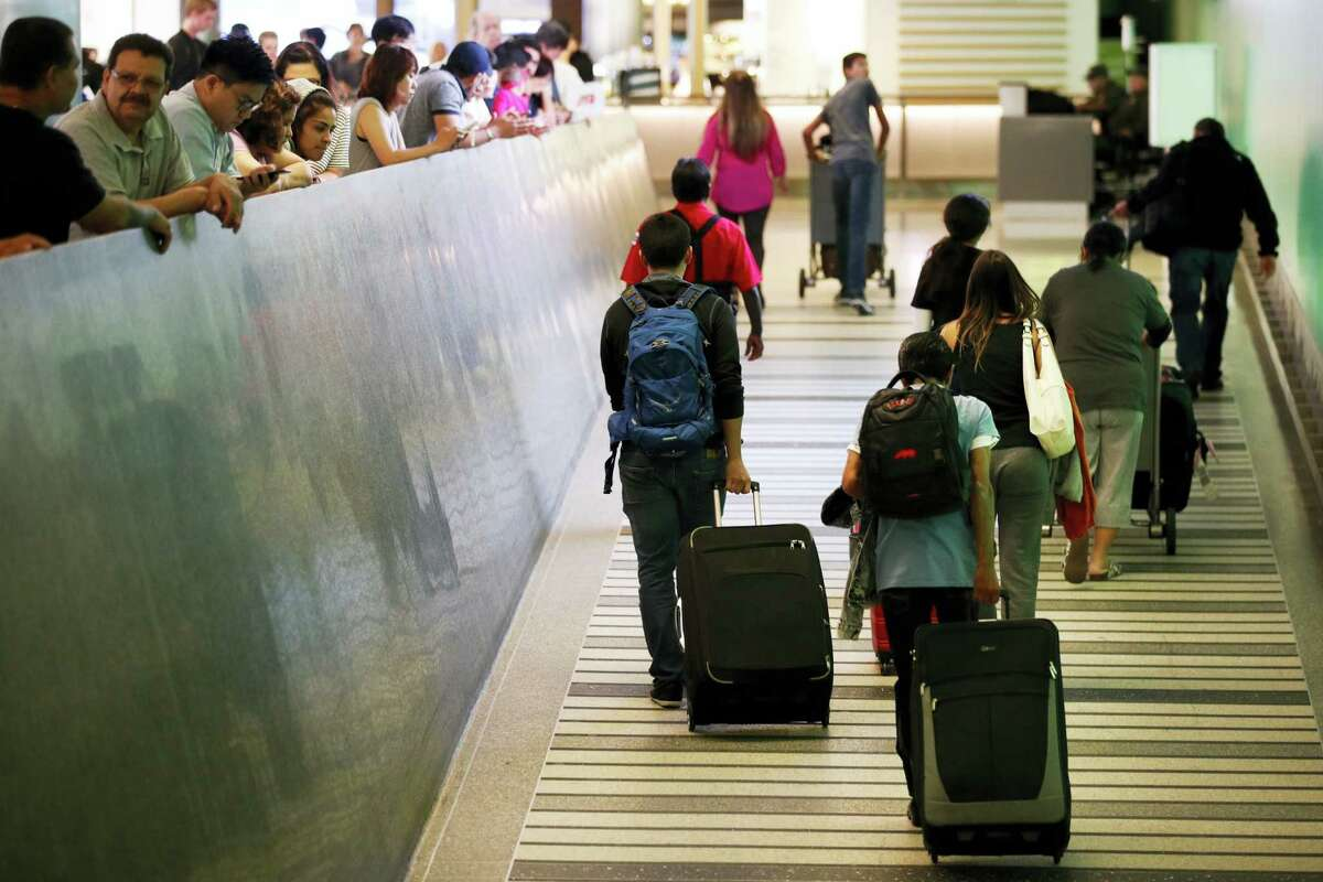 Travelers make their way up the arrival ramp at the Tom Bradley International Terminal at the Los Angeles International Airport Thursday, June 29, 2017, in Los Angeles. After months of wrangling, tighter restrictions on travel to the U.S. from six mostly Muslim nations take effect Thursday evening after the Supreme Court gave its go-ahead for a limited version of President Donald Trump's plans for a ban. (AP Photo/Jae C. Hong)
