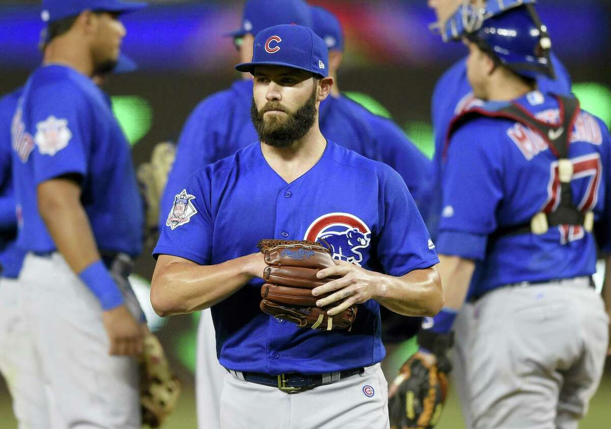 Chicago Cubs starting pitcher Jake Arrieta, center, walks to the dugout after he was pulled from the game during the fifth inning of a baseball game against the Washington Nationals on June 27, 2017 in Washington. The Nationals won 6-1.