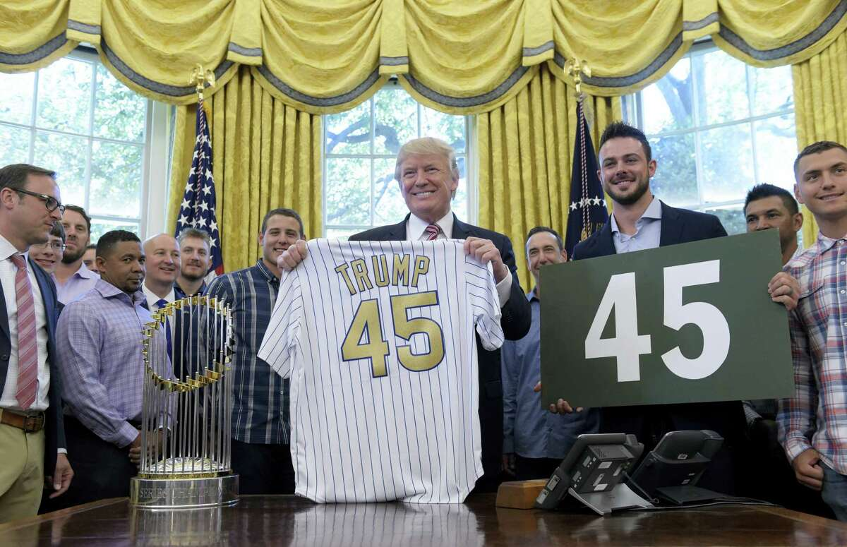 """President Donald Trump holds a Chicago Cubs jersey as he meets with members of the 2016 World Series Champions Chicago Cubs, Wednesday in the Oval Office of the White House in Washington. Cubs third baseman Kris Bryant holds a """"45"""" sign."""