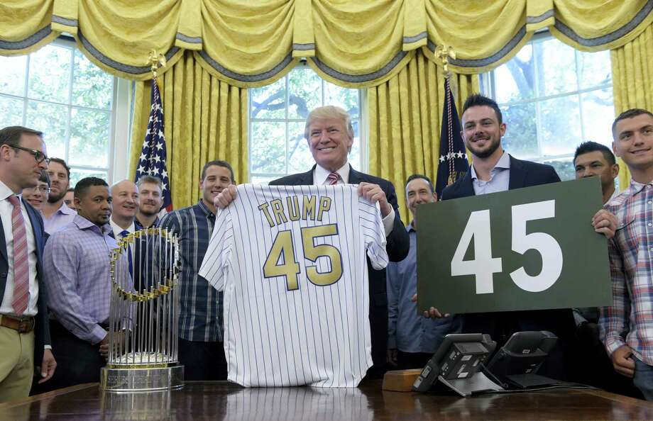"""President Donald Trump holds a Chicago Cubs jersey as he meets with members of the 2016 World Series Champions Chicago Cubs, Wednesday in the Oval Office of the White House in Washington. Cubs third baseman Kris Bryant holds a """"45"""" sign. Photo: Susan Walsh — The Associated Press  / Copyright 2017 The Associated Press. All rights reserved."""